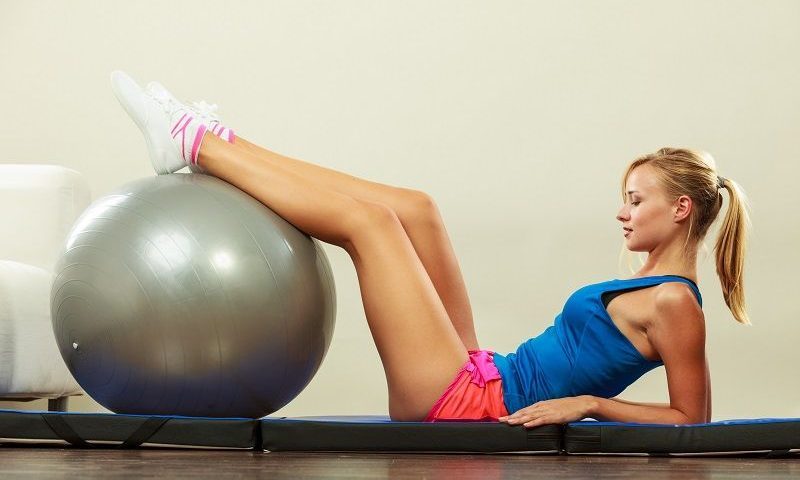 girl-using-exercise-ball-in-room-large